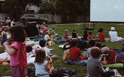 Movie nights - backs of children watching outdoor movie