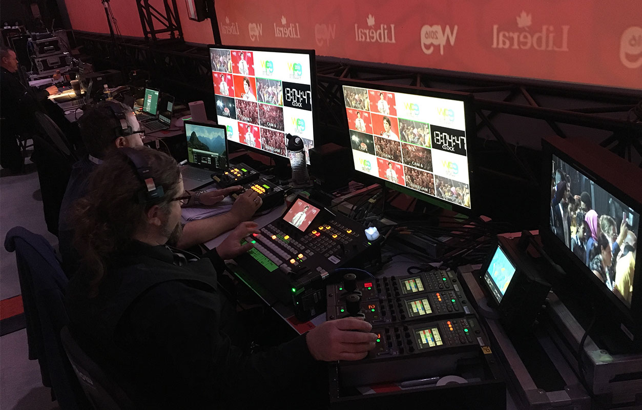 Bespoke AV technicians in booth, watching monitors and boards at Liberal Party event