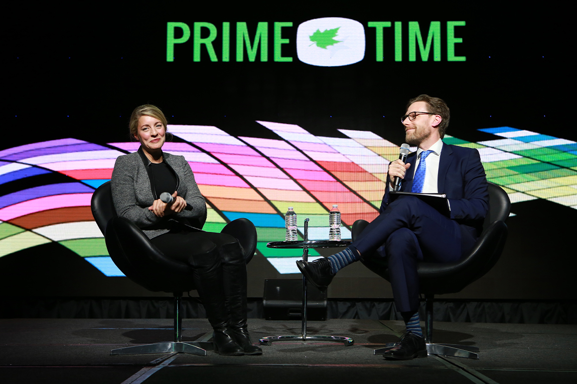 Man and woman chatting on stage at CMPA Prime Time