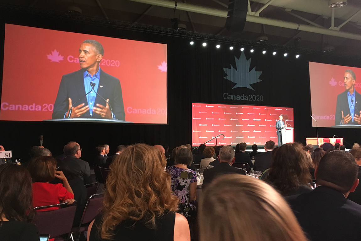 Barack Obama on stage with jumbo screens to side