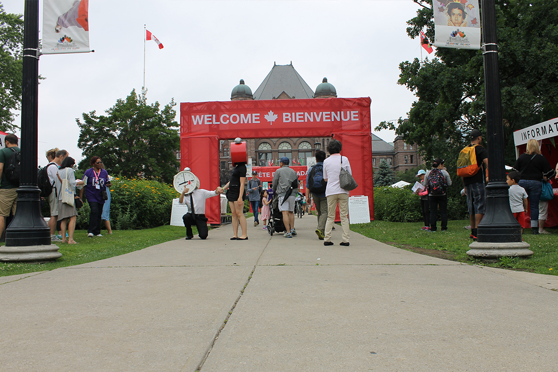 People entering through welcome arch at Fete Du Canada event