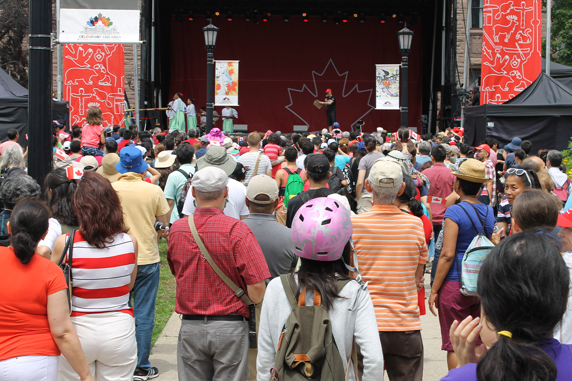 Back of audience listening to host at Fete Du Canada