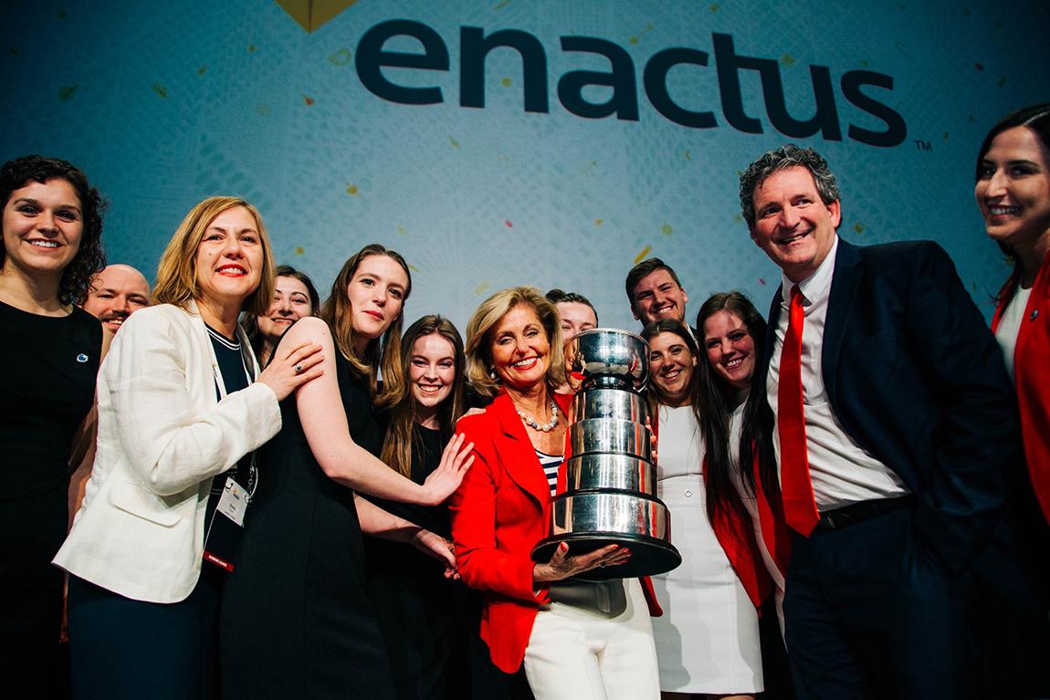 Enactus team photo with trophy