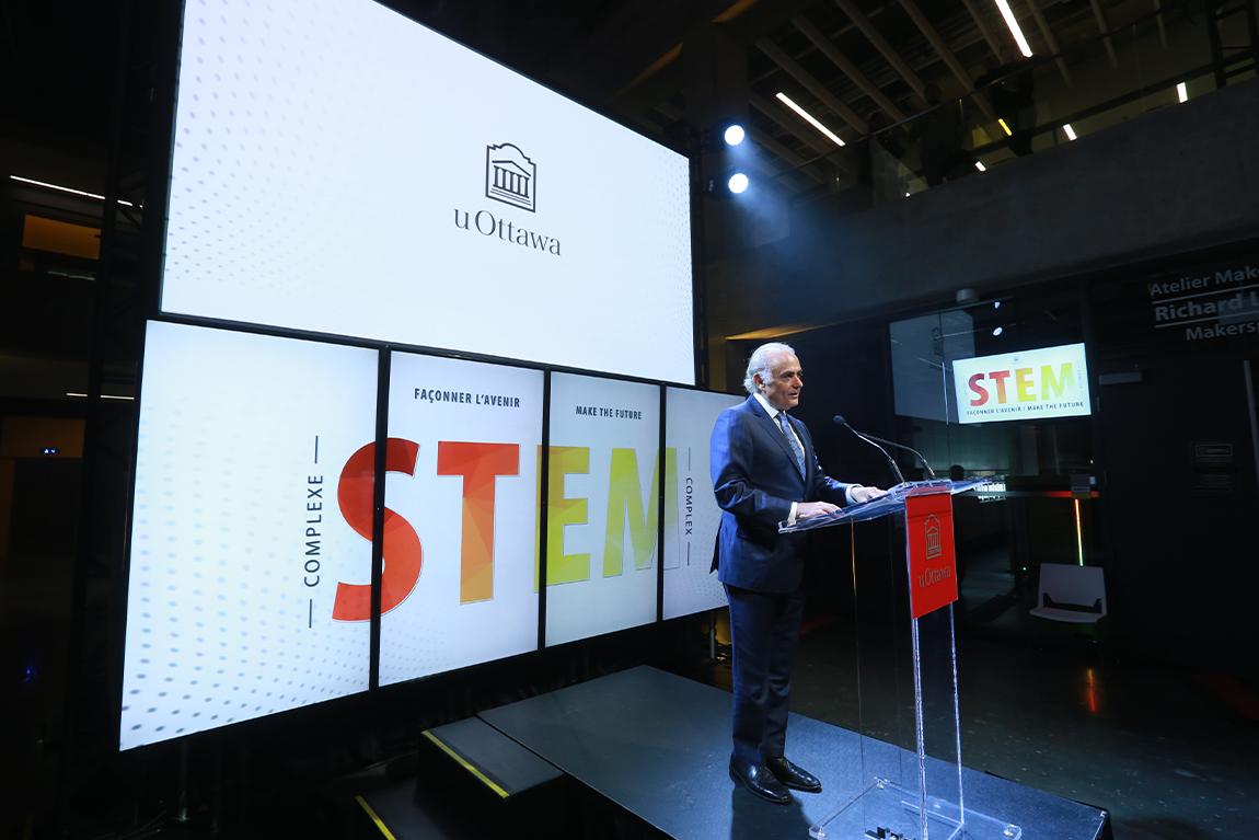 Presenter at podium with U of Ottawa STEM Complex on monitors