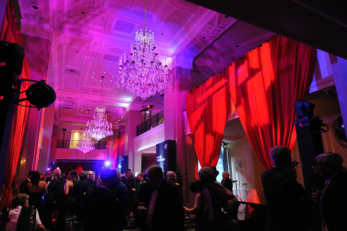 Venue with chandelier, event lighting, and attendees at TIFF TRibute Gala
