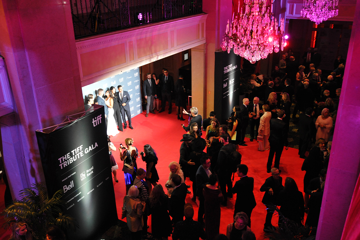Crowd on red carpet with group at step-and-repeat, TIFF Tribute Gala