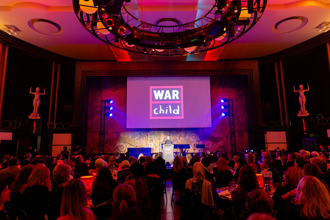Person speaking behind podium at War Child benefit