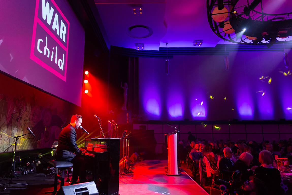 Pianist singing on stage at War Child benefit