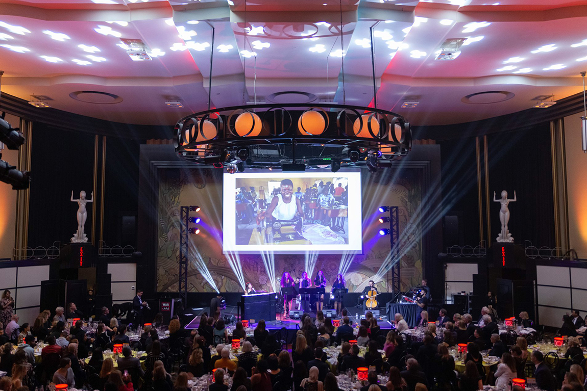 venue set-up at War Child benefit with performers on stage and audience at tables