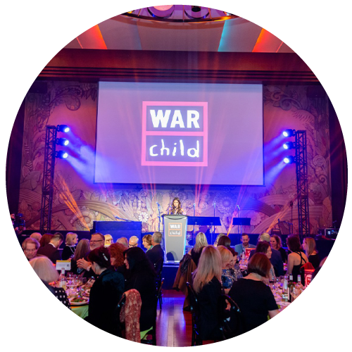 Speaker on stage at War Child Canada event with attendees in foreground