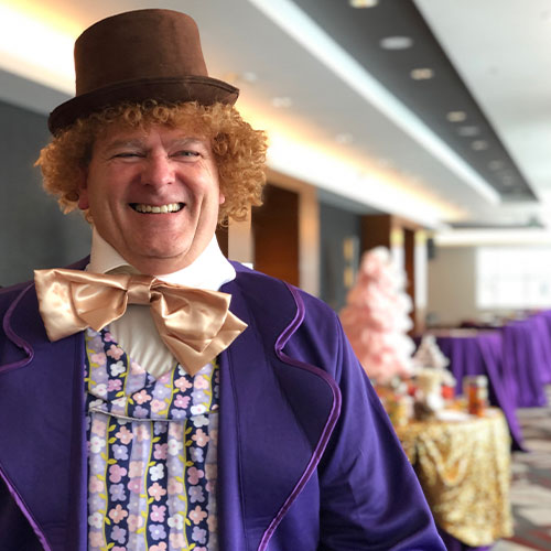 Bespoke teammate dressed in quirky purple suit at CSAE Holiday Luncheon