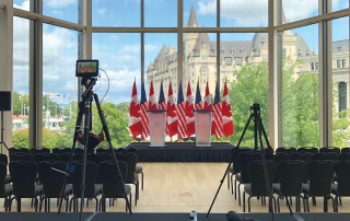 Meeting room with stage, podium, and flags with Ottawa landscape in background