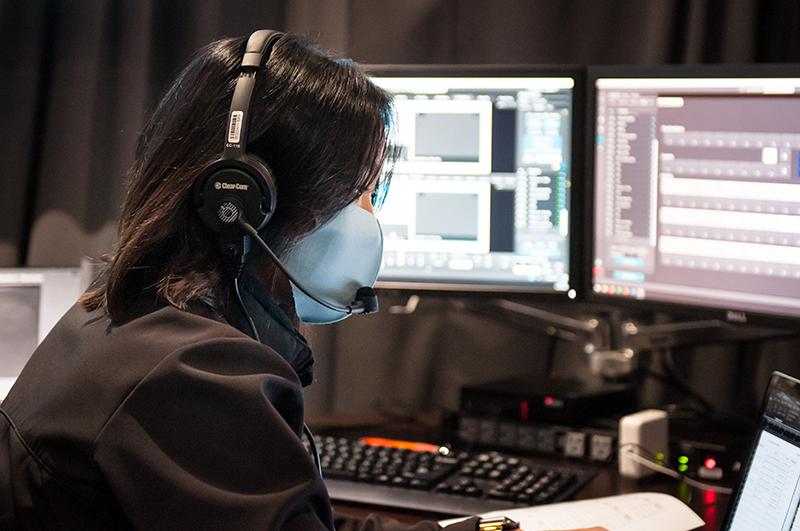 Bespoke AV technician in mask working on laptop with monitors in background