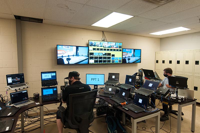 Bespoke AV control room full of laptops, monitors, technicians